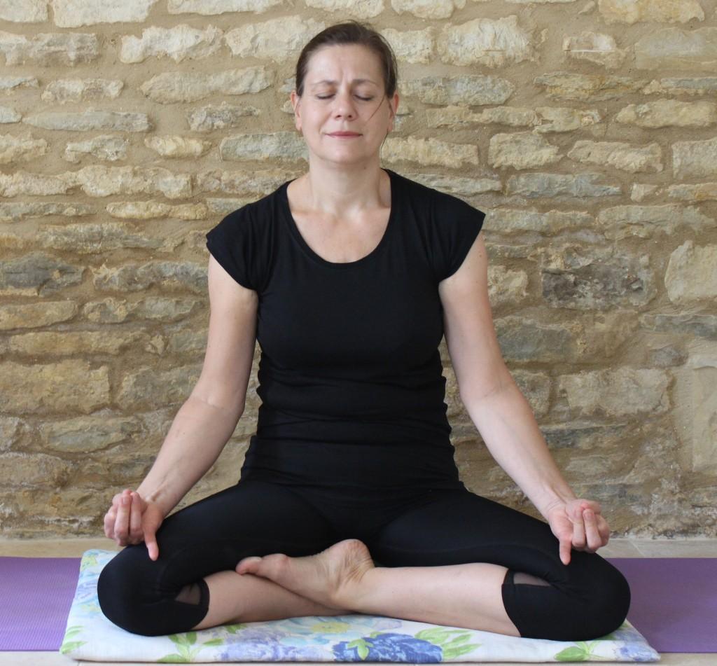 Deborah King demonstrating a posture for use in the online meditation classes